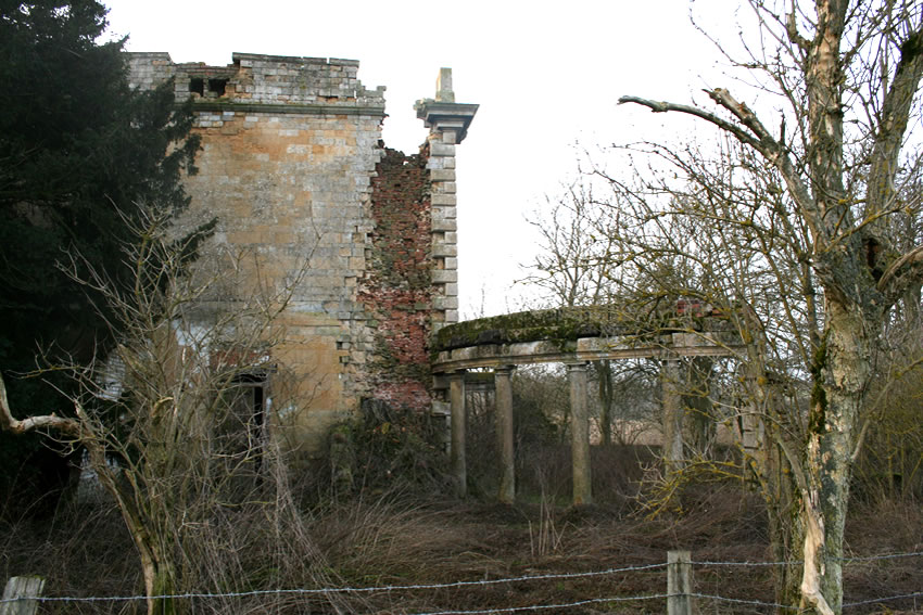 This side view shows the once-impressive, curved colonnade leading to the main entrance.
